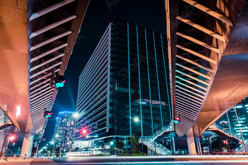 View of the modern pedestrian bridge accross the junction leading to the big building at night Fotobehang