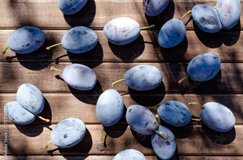Fotografie, Obraz Top vie of juicy damsons plums on the wooden table as a background