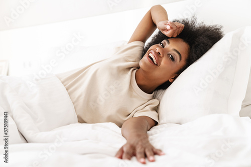 Fototapeta Beautiful young african woman lying in bed