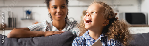 selective focus of young african american nanny behind excited girl laughing whi Canvas Print