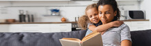 Horizontal Image Of African American Girl Embracing Nanny Sitting On Couch And Reading Book In Kitchen