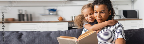 Fototapeta horizontal image of african american girl embracing nanny sitting on couch and r