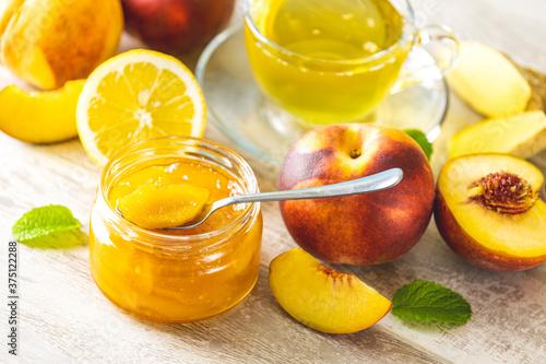 Fotografia Fresh homemade peach jam in glass jar on a light gray wooden background
