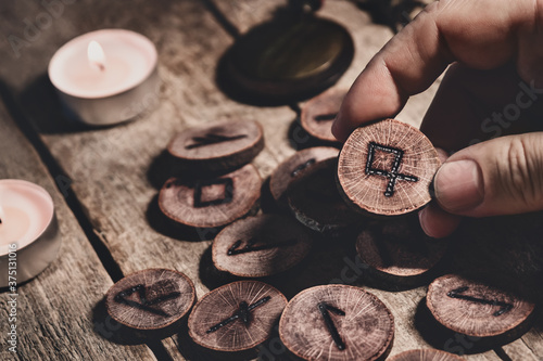 Fotografie, Obraz Hand holding wooden runes or futhark, esoteric and spirituality, reading and for