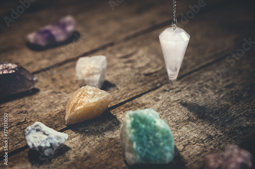 Crystal Pendulum with healing gemstones on wooden table, spirituality and esoter Canvas