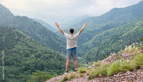 Photo Young man standing on the slope of the mountain raised his hands up and admires the beautiful view of the mountain panorama