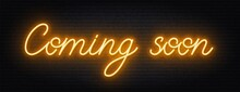 Coming Soon Neon Script Sign On Brick Wall Background .