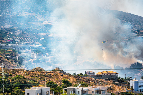 Fotografering Mountain area and village in fire, smoke in the air.