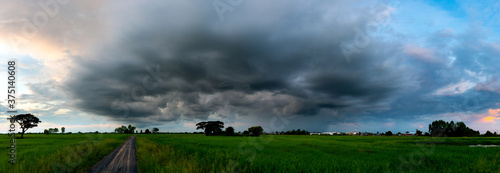 Photo Panorama Super storm with sun light , Dark sky and dramatic black cloud before rain