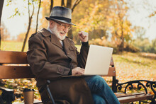 Profile Side Photo Of Ecstatic Old Man Sit Bench Walk Stick In Town Center Autumn Nature Park Use Laptop Check Email Win Black Friday Lottery Raise Fists Wear Coat Hat Cap