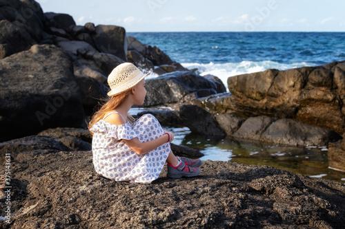 Photo A pretty little girl enjoys the sunny warm day at a rocky coastline