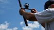 Male hand holds fishing rod on the background of the river close-up. Fisherman holds a fishing rod. River fishing.