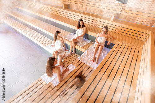 Obraz Group of women relaxing in the sauna uses spa treatment - fototapety do salonu