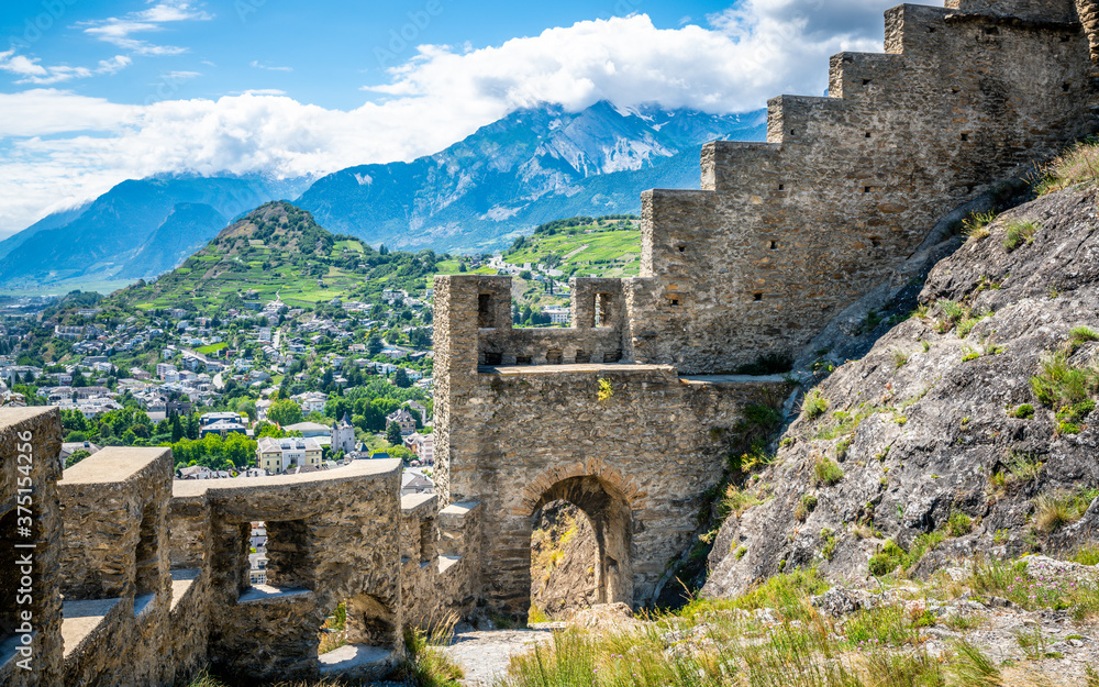 Fototapeta Entrance door and wall of the ruins of Tourbillon castle and Sion hill and city panorama in background Sion Valais Switzerland
