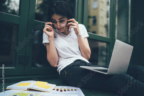 Fotografie, Tablou Amazed female student in classic glasses shocked with noted information in educa