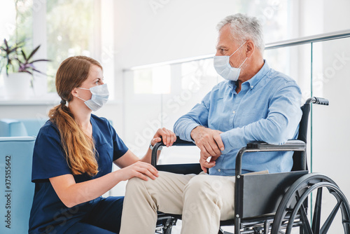 Young nurse taking care of mature male patient on wheelchair in hospital Canvas