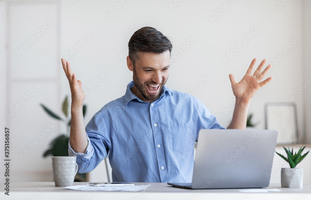 Fototapeta Happy male entrepreneur emotionally celebrating business success with laptop in office