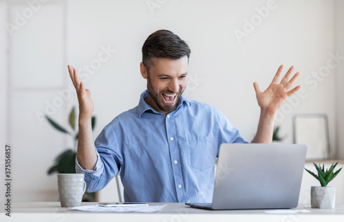 Happy male entrepreneur emotionally celebrating business success with laptop in office