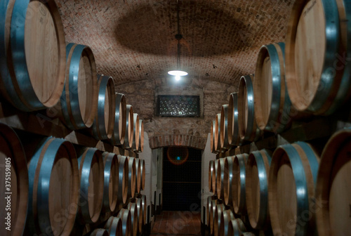 Fotomural Wine barrels stored in a wine cellar of world famous Amarone red wine, produced in the Valpolicella Region (Verona Province, Veneto Region, Northern Italy)
