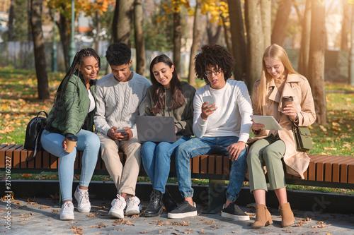 Addicted teenagers using gadgets while spending time in park Billede på lærred
