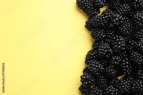Fényképezés Tasty ripe blackberries on yellow background, flat lay