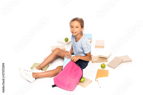 schoolgirl sitting near apples and putting book in backpack isolated on white