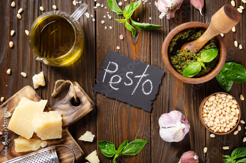 Fotografia Food background of genovese pesto sauce in wooden mortar and its ingredients on