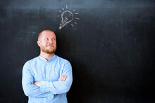 Pensive Young Businessman Standing Over Chalkboard Background With Light Bulb.