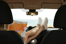 Young Woman With World Map In Car, Back View. Road Trip