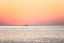 A Boat And The Sun On The Horizon At Sea