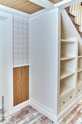 Fotografia Built-in bookcase under a wooden staircase with white balusters
