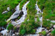 Small Waterfall On Green Grass