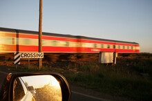 Train Speeding Through A Railway Crossing In The Late Afternoon Light