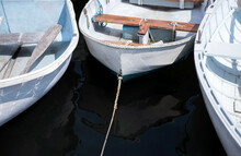 Trio Of Floating Rowboats Are Tied To A Dock