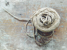 A Spool Of Twine Or Yarn On A Wooden Table