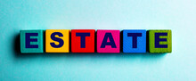 The Word ESTATE Is Made Up Of Colored Wooden Cubes On A Light Blue Background. Financial Concept