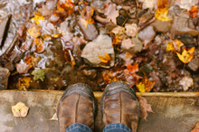 Feet On Bridge With Stream And Fallen Maple Leaves In Autumn