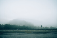Creepy Empty Road On Background Of Misty Dense Forest On Hills