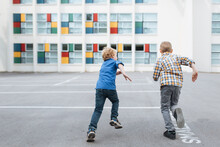 Two Boys Running Towards A Sch...