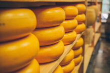 Cheeses Stacked On A Shelf In A Dairy.