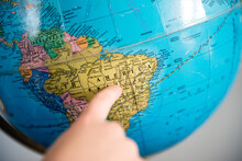 Child Points To The Country Of Brazil On An Old School Globe