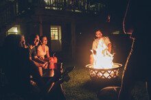 Mid 20s Aged Friends Gathered Around A Campfire During House Party