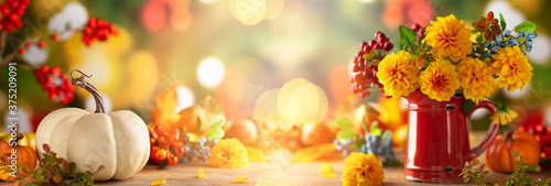 Obraz Autumn floral still life with beautiful yellow dahlia in vintage red jug and pumpkins on the table. Autumnal festive concept. - fototapety do salonu