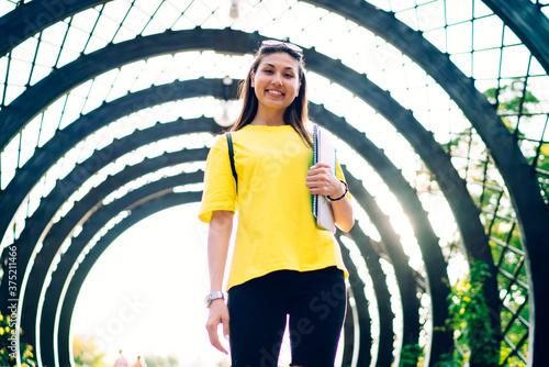 Fototapeta Half length portrait of cheerful asian hipster girl in trendy activewear standin