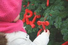 A Girl Holds The Letter T That Hangs From A Decorated Christmas Tree