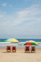 Two Colourful Parasols With Chairs On A Empty Beach With The Sea On The Background