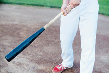 Baseball Player Holding Bat In...