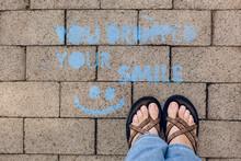 Looking Down On Sidewalk Grafiti Next To A Woman's Feet.