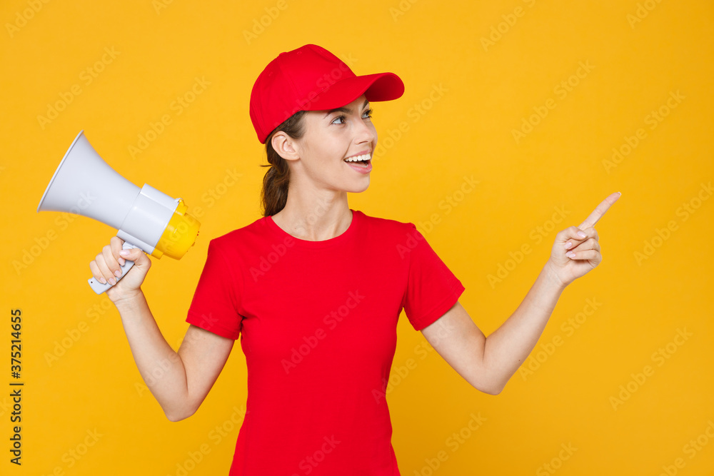 Fototapeta Fun crazy delivery employee woman in red cap blank t-shirt uniform work courier in service hold megaphone announces discount pointing finger aside on workspace copy space isolated on yellow background