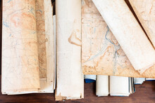 Pieces Of An Antique Map And Scrolls Sit On A Wooden Table.